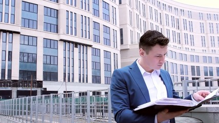 businessman in a suit and white shirt reading business papers