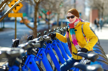 Young beautiful woman ready to rent a city bike