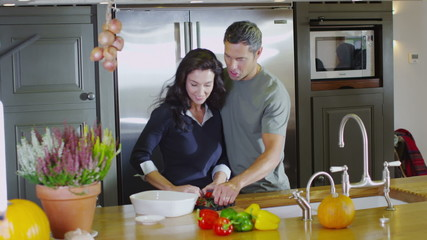 Happy affectionate couple preparing food together in the kitchen at home
