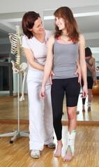 Physiotherapeutin steht neben Patientin mit Fußverletzung