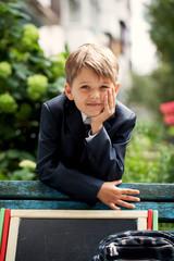 Portrait of a school boy in the green park