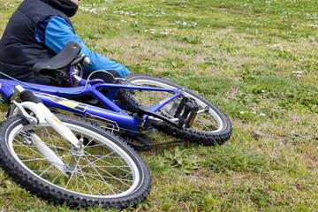 bambino con bicicletta seduto sul prato