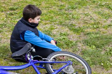 bambino seduto vicino alla bicicletta