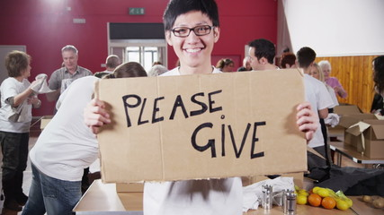"Male charity worker holds up a ""Please Give"" sign to camera"