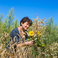 Woman with ears and sunflowers in field