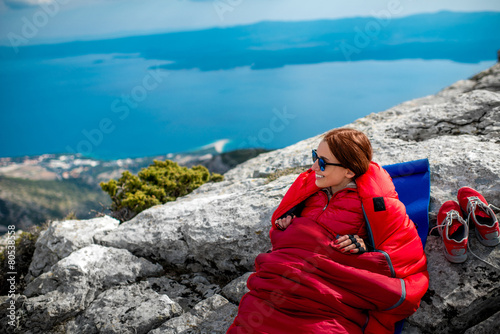 Canvas Alpinisme Woman in sleeping bag on the mountain