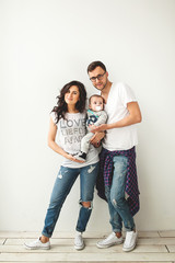 Hipster father, mother holding cute baby boy over white backgrou