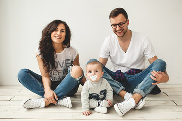 Young hipster father, mother and baby boy on wooden floor