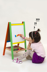 Musingly girl glues magnetic letters on white board