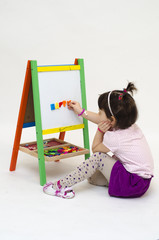Musingly girl glues magnetic letters on white board isolated