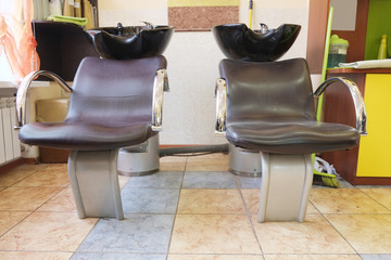 Black bowl for head washing and chairs in hairdresser salon