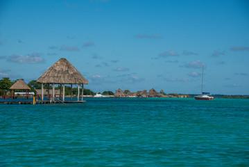 Caribbean scene with hut and Sailboat. Bacalar, near tulum. Trav