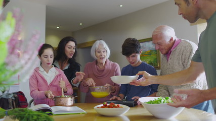3 generations of happy family preparing a meal together in the kitchen at home