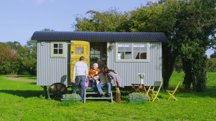 Cheerful family relaxing together outside quaint caravan in a natural setting