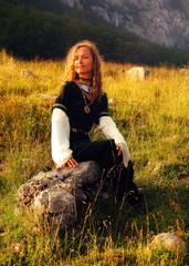mystical medieval maiden sitting on a wild meadow stone