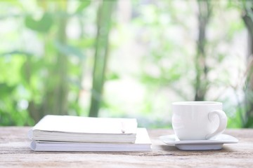 Notebook  and  white cup on wooden table
