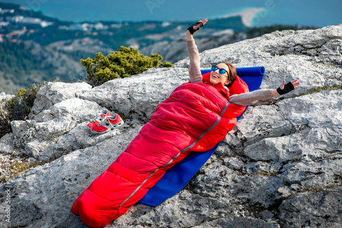 Woman in sleeping bag on the mountain - 80541792