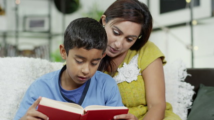 A mother teaches her son how to read