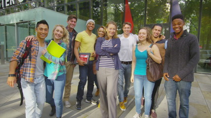 Portrait of cheerful diverse student group outside college building