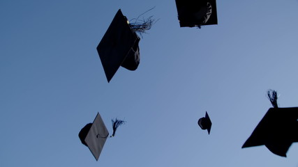 Graduation caps are tossed into the air on a bright sunny day
