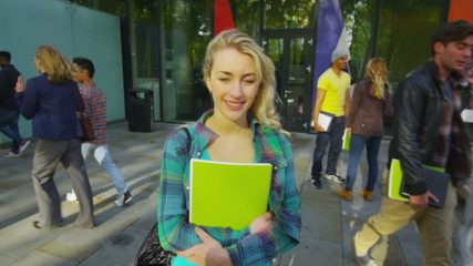 Portrait of cheerful young student standing outside college building