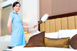 Chambermaid dusting in Asian hotel room