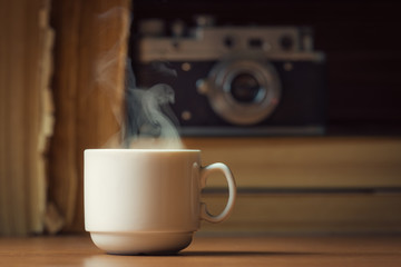 Cup of hot coffee with steam over defocused books and vintage ca