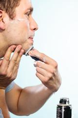 Man shaving with razor face profile