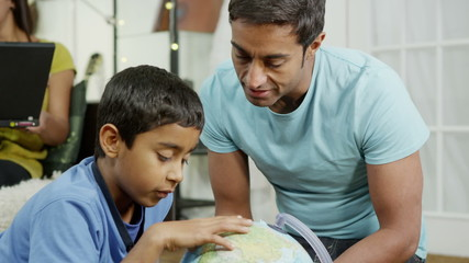 Father and son using a globe to look at countries around the world
