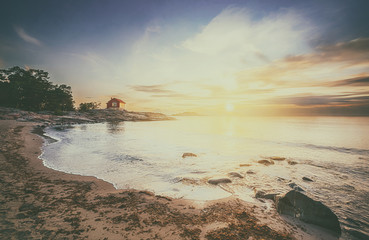 Red cottage at seafront in sunrise with vintage feeling