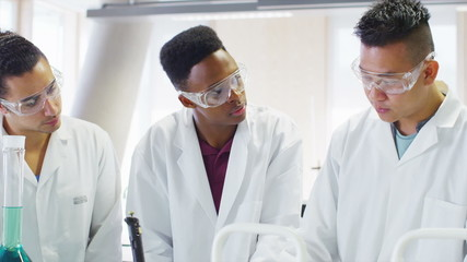 Young group of university students working together in science class