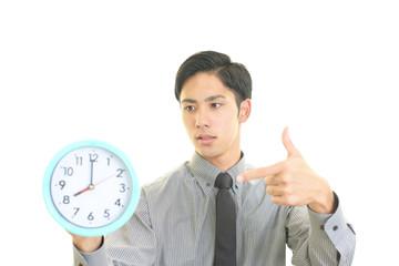 時計を指差すビジネスマン