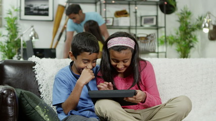 Young boy and girl playing on a digital tablet