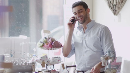 Attractive male business owner on the phone from behind the counter of his shop