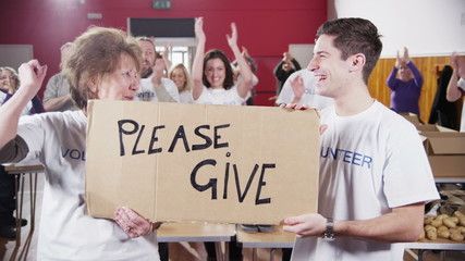 "2 Charity workers hold up a ""Please Give"" sign as their fellow workers applaud"