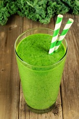 Green kale smoothie in a glass with straws on rustic wood