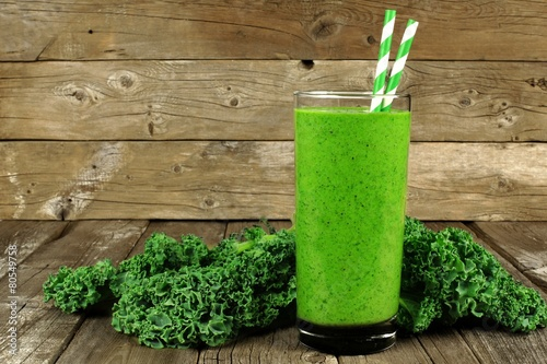 Healthy green smoothie with kale in a glass against rustic wood