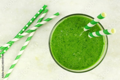 Green smoothie downward view in glass with straws - 80549769