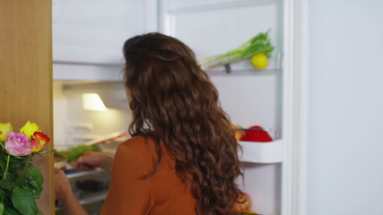 Breaking the diet - hungry woman goes to the fridge to snack on some cake