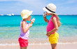 Little adorable girls eating ice cream on tropical beach - 80550749