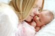 Leinwanddruck Bild - Happy Mother Snuggling Newborn Baby in Bed