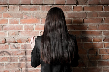 Rear view of a woman with long brown hair against red brick