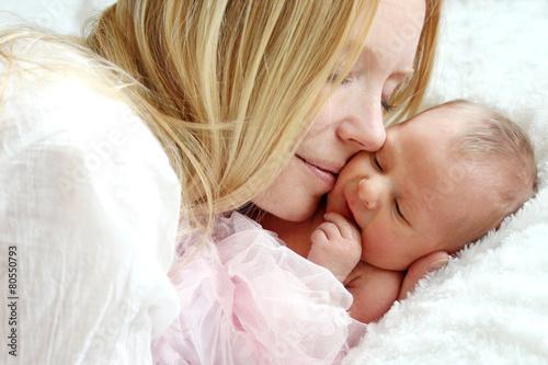 Leinwanddruck Bild Happy Mother Snuggling Newborn Baby in Bed