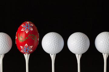 Golf balls and egg on a black glass desk