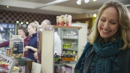 Shopkeeper takes a credit card payment from a cheerful female customer