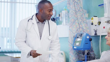 Caring doctor chatting with an elderly female patient at her bedside