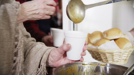Feeding the hungry - eager hands take soup and bread