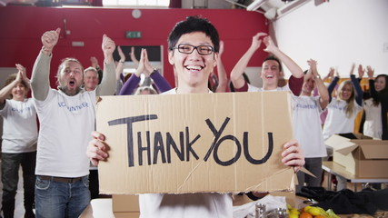 "Charity worker holds up a ""Thank you"" sign as his fellow workers applaud"