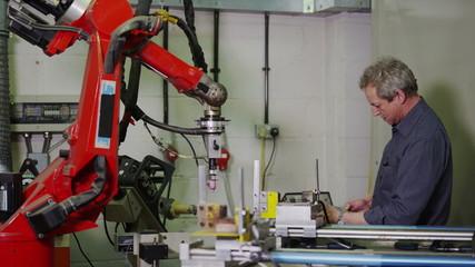 Mature male machine operator working in a factory
