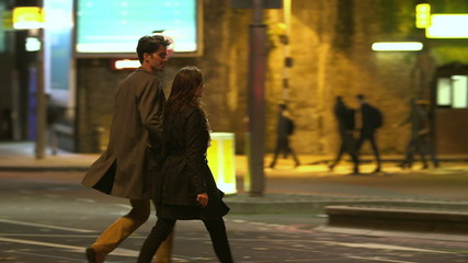 Attractive couple in casual dress crossing the road in London at night